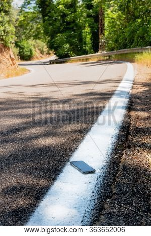 Vertical Color Image With A High Angle View Of A Forgotten Or Lost Smartphone On The Roadside On The