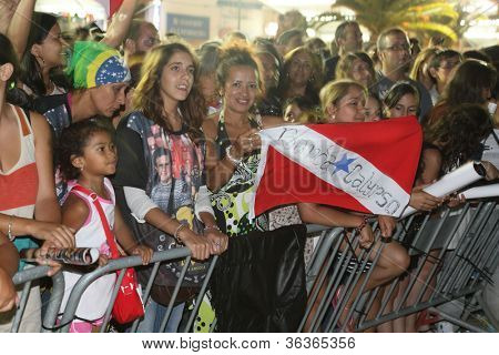 OLHAO, PORTUGAL - AUGUST 12:  Audience observe banda calypso show onstage at seafood festival on August 12, 2012 in Olhao, Portugal.