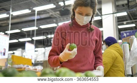 Beautiful Girl In Rubber Gloves And Medical Mask Carefully Selects Lime For Prevention Diseases Of C