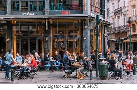Brussels, Belgium: Group Of Happy People Meeting At Street Cafe Area For Drinks At Busy Evening On A