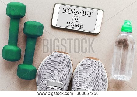 Flat Lay On A Light Background: Gray Sneakers, Green Dumbbells, Bottle Of Water, And A Smartphone Wi
