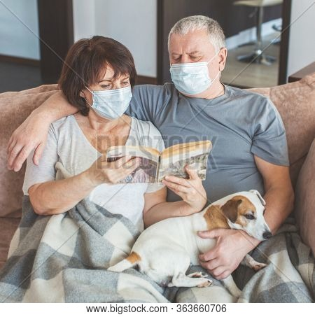 Couple old aged senior people at home with seasonal winter cold illness disease sit down on the sofa Reading book. Elderly couple in medical masks during the pandemic Coronavirus CoVid-19