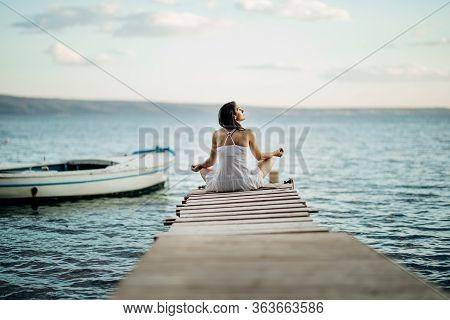 Young Woman Sitting Alone At The Beach.self Isolation In Nature.coronavirus Quarantine Lockdown Beac