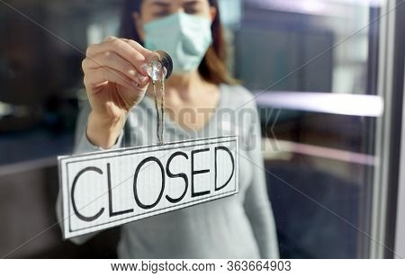 small business, pandemic and service concept - young woman in protective medical face mask hanging banner with closed word on door or window