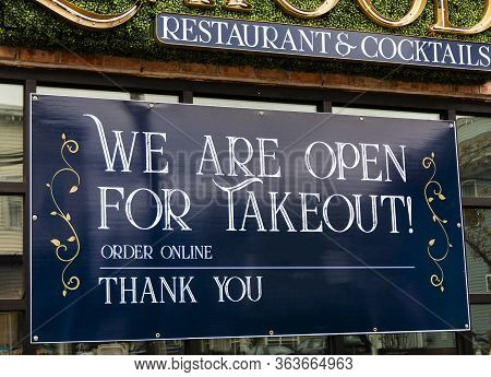Large Blue Sign In Window Of Restaurant Reads We Are Open For Takeout Order Online And Thank You Dur