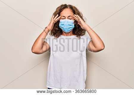 Middle age woman wearing coronavirus protection mask for covid-19 epidemic virus with hand on head, headache because stress. Suffering migraine.
