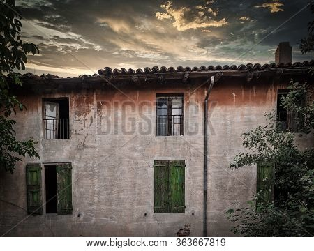 Rundown Building With Green Shutters At Sunset Under Stormy Clouds Outside Of Bologna Italy