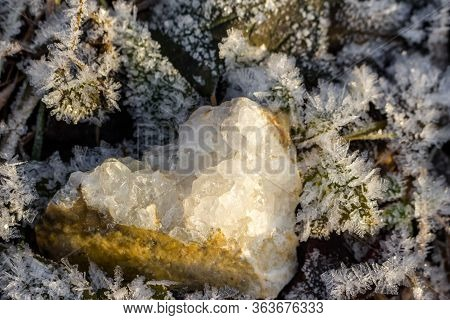 Rock Crystal (quartz) On The Background Of Crystalline Hoarfrost On The Grass