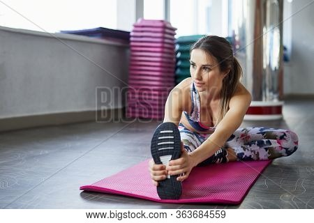 Healthy Woman Fitness Mat Doing Warmup Exercise. Fit Woman Sitting On Exercise Mat Stretching.
