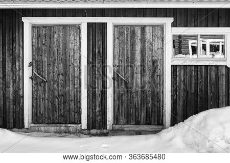 An Old Wooden Building Has Two Doors And A Window Beautifully Framed With White Painted Wood.
