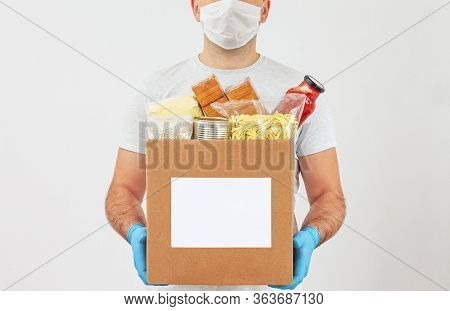Coronavirus Donation Box. Delivery Food. Volunteer. Food Help. Delivery Man In A Mask And Medical Gl
