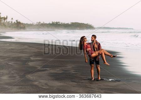 A Happy Couple Walks Along The Beach At Sunset. Lovers On The Coast. Couple On Their Honeymoon. Beau