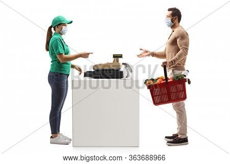 Full length profile shot of a man paying at a cash register and wearing a protective face mask isolated on white background