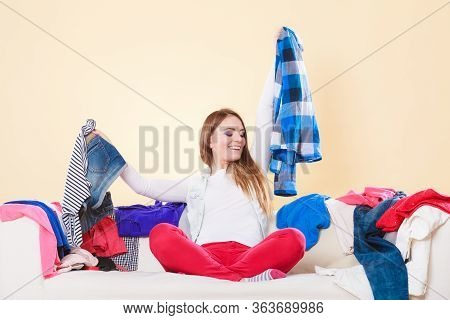 Happy Woman Sitting On Sofa Couch In Messy Living Room Holding Clothes. Young Girl Surrounded By Man
