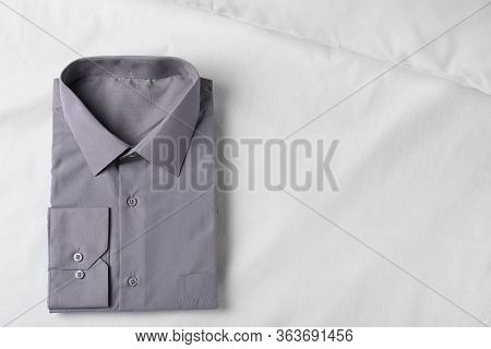 Stylish Grey Shirt On White Fabric, Top View With Space For Text. Dry-cleaning Service