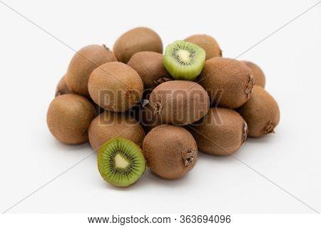 Pile Of Whole And Cut Kiwi Fruits Isolated On White Background. Bunch Of Fresh Ripe Kiwifruits. Heal