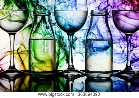 Wine Glasses And Bottles In A Row With Colorful Light Painting Behind, Set Of Wine Glasses With Red,