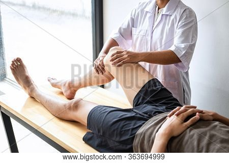 Female Physiotherapist Working Examining Treating Injured Leg Of Male Patient, Doing Exercises The R