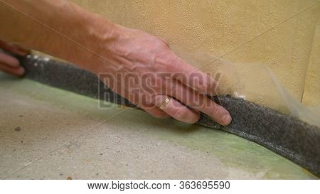 Worker Glues Damper Tape Before Laying The Floor. Reinforcing Tape For Drywall. Damper Tape For Scre