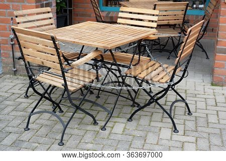 Chairs And Table Locked With A Chain In A Street Cafe, Which Is Forbidden To Open Due To The Coronav