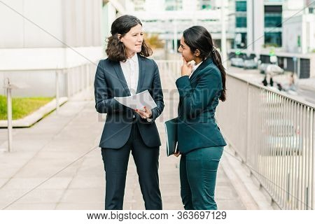 Professional Businesswomen Discussing Papers. Full Length View Of Female Colleagues In Formal Wear S