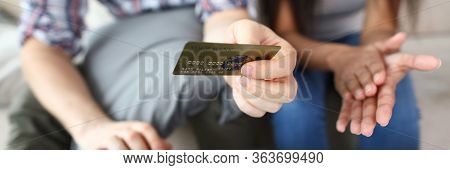 Close-up Of Males Hand Holding Credit Card. Man And Woman Shopping Online, Buying Tickets Using Plas