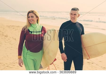 Content Couple With Surfboards Walking On Beach. Cheerful Man And Woman In Wetsuits Holding Surfboar