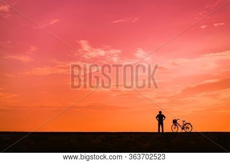 The Silhouette Of A Cyclist Against The Background Of The Orange Dawn Sky. A Man Stands Next To A Bi