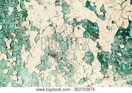 Texture background - peeling paint on the old rough concrete surface, peeling paint texture.Peeling paint texture. Texture concrete industrial background - light yellow and green peeling paint on the old rough concrete surface, peeling paint texture