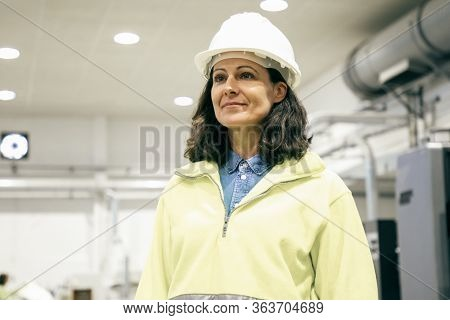 Positive Confident Female Foreman Walking On Plant Floor. Middle Aged Woman In Uniform And Hardhat S