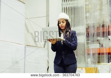 Low Angle View Of Focused Manager Using Laptop At Factory. Concentrated Asian Employee Holding Open