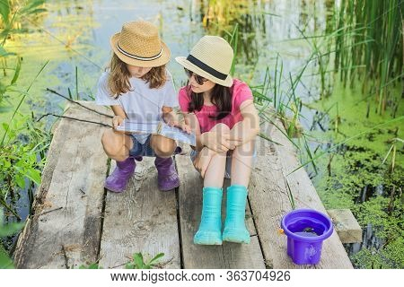 Children Two Girls Resting Playing Reading Their Notebook In Nature. Kids Sitting On Wooden Lake Pie