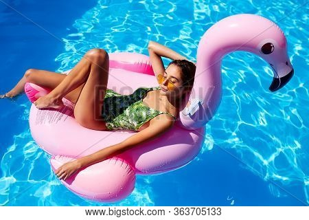 Young Smiling Fitted Girl In Bikini Relax Chilling On Pink Inflatable Flamingo In Swimming Pool. Att