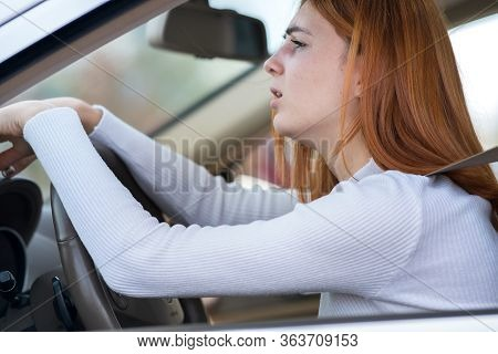 Sad Tired Yound Woman Driver Sitting Behind The Car Steering Wheel In Traffic Jam.