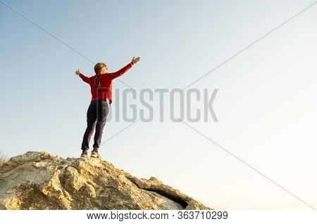 Young Woman Hiker Standing Alone On Big Stone In Mountains. Female Tourist Raising Her Hands Up On H