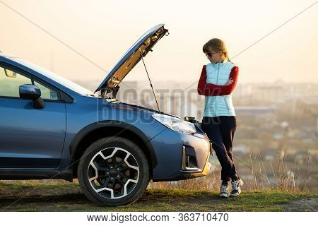 Young Woman Standing Near Broken Down Car With Popped Up Hood Having Trouble With Her Vehicle. Femal