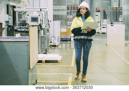 Focused Female Technician With Open Laptop At Printing House. Concentrated Factory Employee Walking