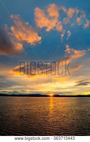 Sea sunset landscape. Sea water surface lit by sunset light. Summer sunny water scene in picturesque tones. Sea summer nature with mountains at the horizon - panoramic view.Sea sunset landscape - sea water lit by sunset summer light. Summer sea water