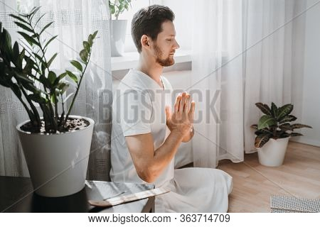 Young Man Meditating At Home On The Floor, Sitting In The Lotus Position With Closed Eyes And Foldin