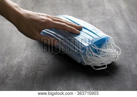 Hand Holds Blue Medical Masks. Disposable Masks For Protection Lie On Black Background. Typical Surg