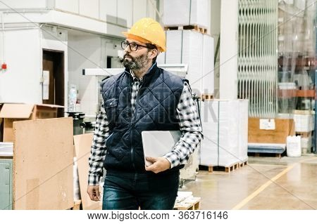 Concentrated Technician Walking With Laptop At Printing House. Focused Factory Employee At Workplace