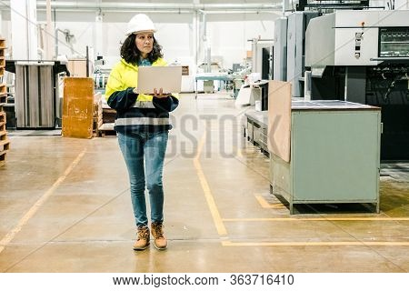 Focused Technician With Open Laptop Inspecting Factory. Concentrated Factory Employee Walking At Wor