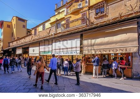 Florence, Tuscany, Italy, March 30, 2019: Many Tourists Enjoy The Day And Walk On The Famous Ponte V