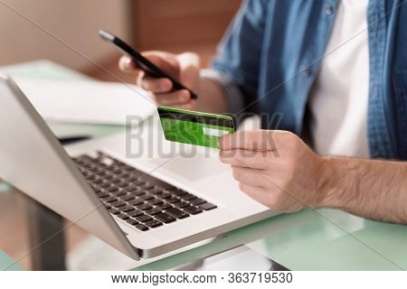 Closeup Of Young Caucasian Manat Using Bank Credit Card And Smartphone For E-commerce And Online Sho