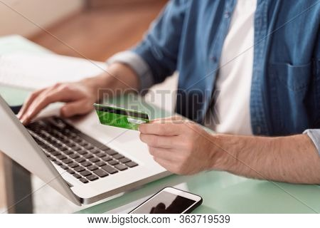 Young Caucasian Man Using Credit Card And Laptop For Online Paying. Using Gadgets For E-banking, E-c