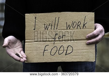 The Unemployed Person Holds In His Hand The Cardboard Tablet With The Inscription I Will Work For Fo