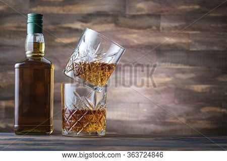 Bottle Whiskey And Two Glass With Bourbon Or Scotch. Rum Or Brandy On Wooden Background