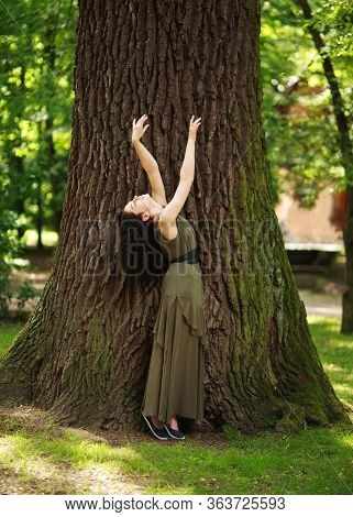 Young Woman In A Green Dress Meditatively Relaxes Near A Large Tree In A Forest Park, Concept Of Pur