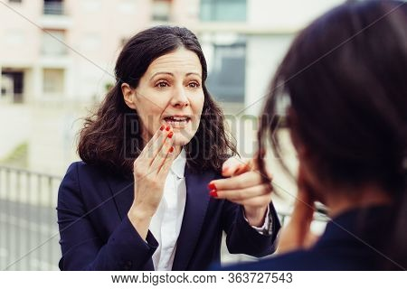 Emotional Businesswoman Talking With Colleague. Excited Middle Aged Businesswoman Pointing With Fing