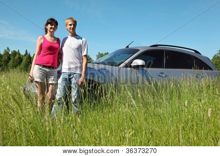 Husband, wife stand near car in field